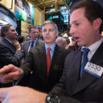 Hilton Worldwide President and Chief Executive Officer Christopher J. Nassetta in the center of the trading crowd as the company's stock opens for trading on the NYSE on Thursday, December 12. Traders wore Hilton Worldwide bathrobes.