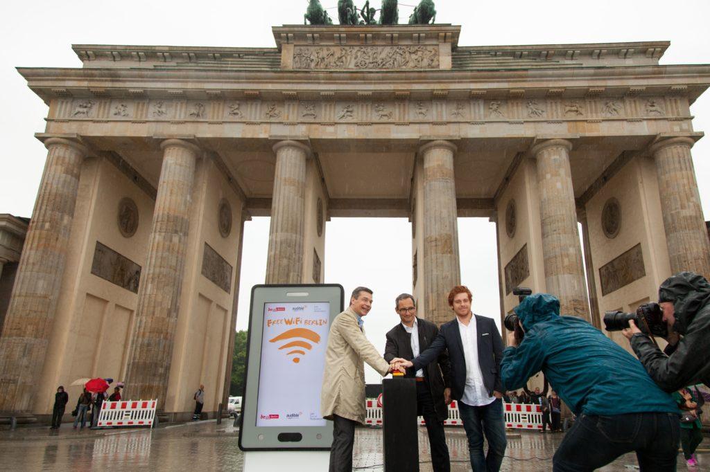 """Am 1. Juni 2016 wurden die ersten 100 Access-Points des Projektes """"Free WiFi Berlin"""" aktiviert. Berliner und Touristen können nun ohne Anmeldung unter anderem am Brandenburger Tor, dem Roten Rathaus oder dem Friedrichstadt-Palast kostenloses und unbegrenztes WLAN nutzen. Das Projekt wurde von der Berliner Senatskanzlei ins Leben gerufen und nach Vertragsunterzeichnung Ende 2015 in Zusammenarbeit mit dem Technik-Partner abl Social Federation und dem Content-Partner Audible umgesetzt. Bernhard Schodrowski (Stellv. Senatssprecher), Nils Rauterberg (Geschäftsführer Audible), Benjamin Akinci (CEO abl Social Federation) (v.l.n.r.) - Foto: Audible"""