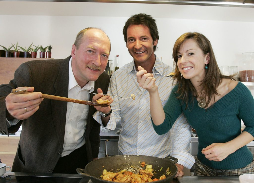 Die Ernährungsberaterin Franca Mangiameli und NRW-Verbraucherschützer Bernhard Burdick genießen Hähnchenbrust süß-sauer mit Sesam – zubereitet von TV-Sternekoch Christian Henze (Mitte). (Foto: ZDG)